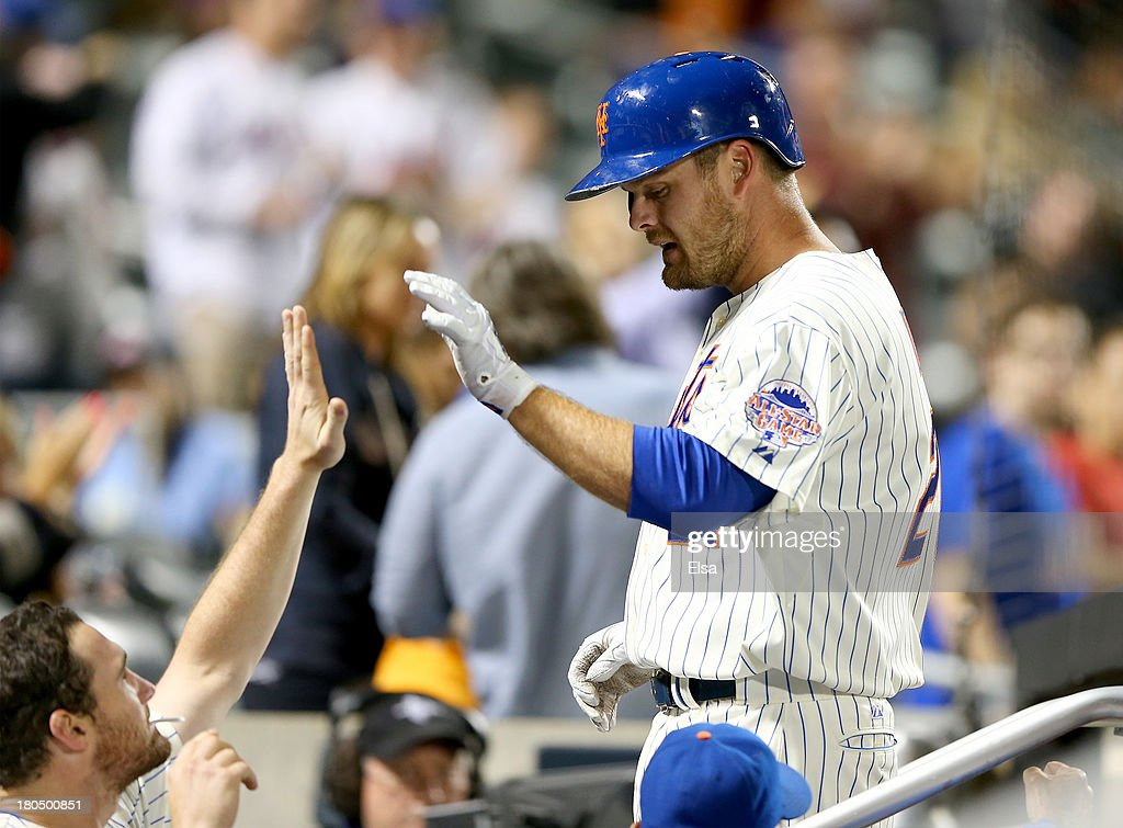 Lucas Duda #21 is congratulated by teammate Daniel Murphy #28 of the New York Mets in the dugout after Duda hit a three run homer in the sixth inning against the Miami Marlins on August 13, 2013 at Citi Field in the Flushing neighborhood of the Queens borough of New York City.