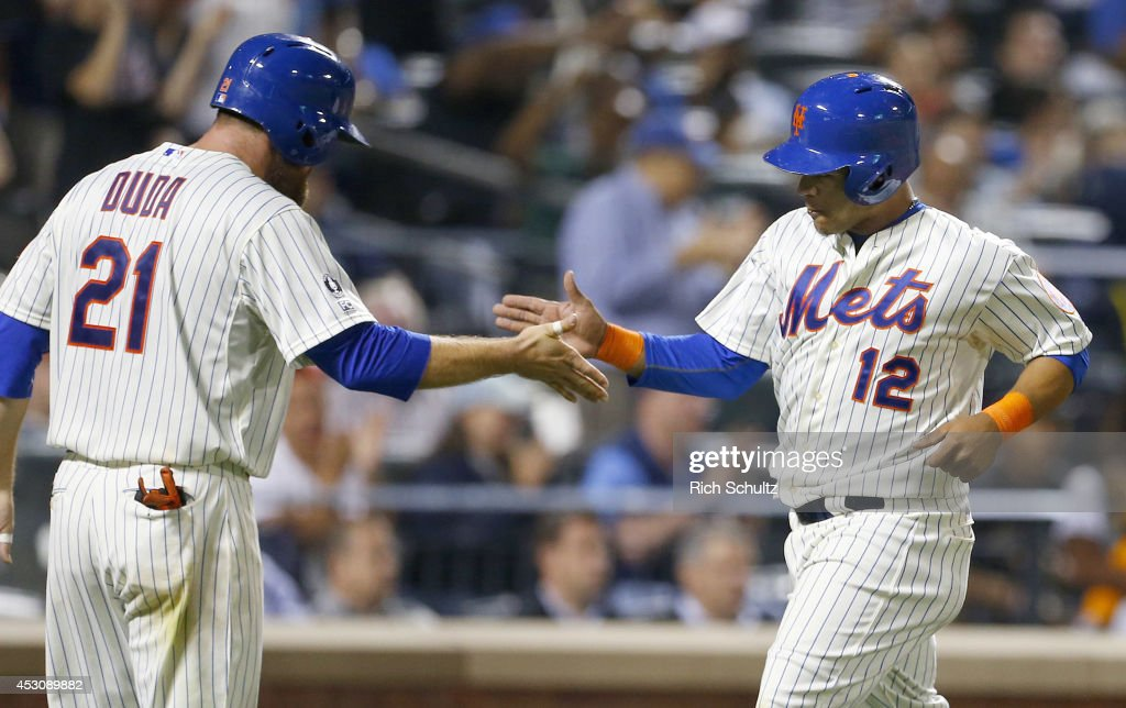 Lucas Duda #21and Juan Lagares #12 of the New York Mets congratulate each other after both scored on a duoble by Wilmer Flores #4 in the seventh inning against the San Francisco Giants on August 2, 2014 at Citi Field in the Flushing neighborhood of the Queens borough of New York City.