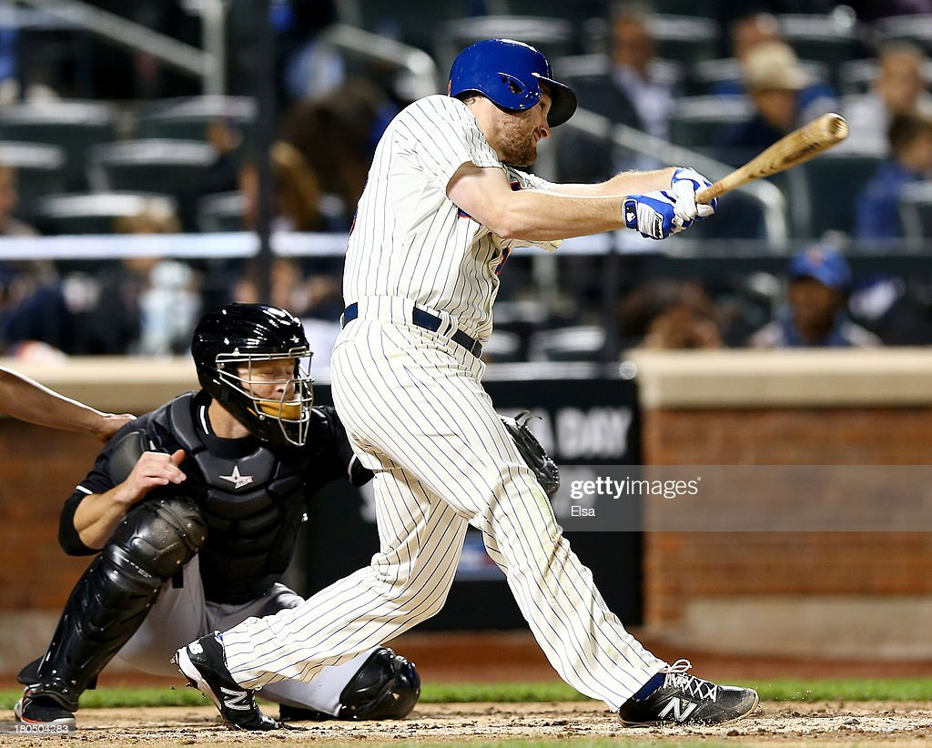 Lucas Duda of the New York Mets hits a three run homer as Koyie Hill of the Miami Marlins catches on August 13 2013 at Citi Field in the Flushing...
