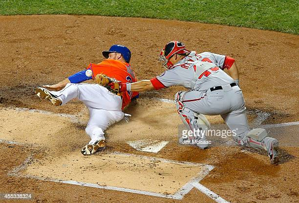 Lucas Duda of the New York Mets is safe at home for a first inning run as Wilson Ramos of the Washington Nationals loses the ball for a fielding...