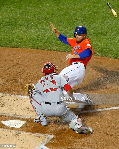 Lucas Duda of the New York Mets scores a first inning run against Wilson Ramos of the Washington Nationals at Citi Field on September 12 2014 in the...