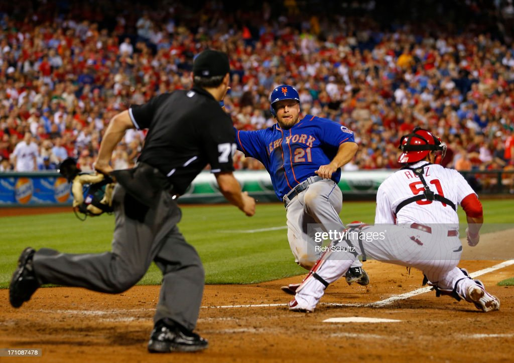 Lucas Duda of the New York Mets scores on a double by teammate Juan Lagares before catcher Carlos Ruiz of the Philadelphia Phillies can apply the tag...