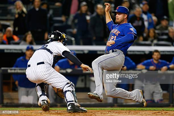 Lucas Duda of the New York Mets slides past John Ryan Murphy of the New York Yankees scoring on Daniel Murphy's RBI double on April 26 2015 at Yankee...