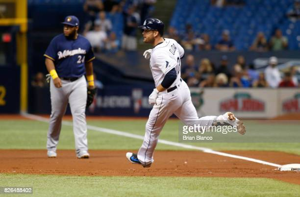 Lucas Duda of the Tampa Bay Rays rounds first base in front of first baseman Jesus Aguilar of the Milwaukee Brewers after hitting a single off of...