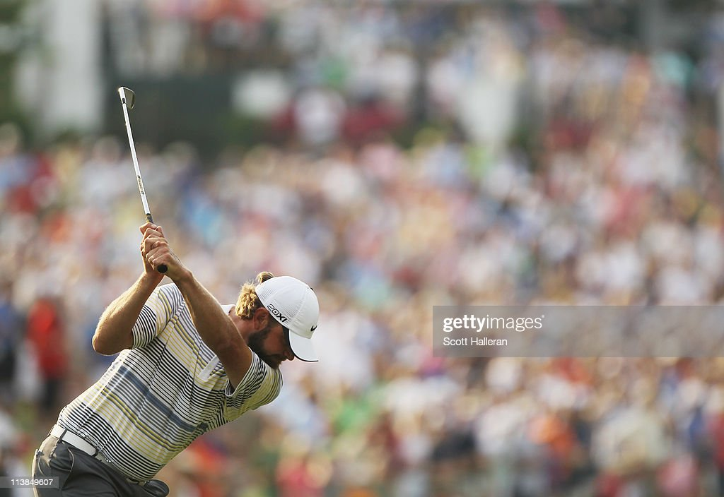 Lucas Glover hits his approach shot on the first playoff hole during the final round of the Wells Fargo Championship at the Quail Hollow Club on May...