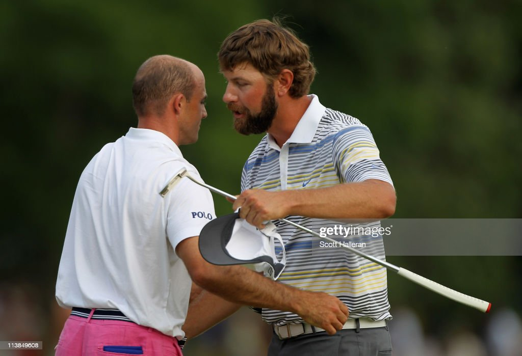 Lucas Glover shakes hands with Jonathan Byrd on the 18th green after defeating Byrd on the first playoff hole during the final round of the Wells...