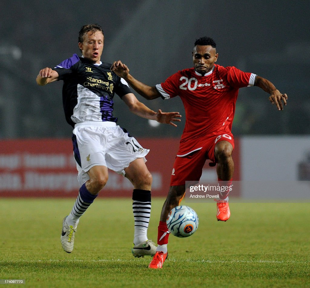 Lucas Leiva (L) of Liverpool competes with Titus Bonay of Indonesia XI during the Pre Season match between Indonesia XI and Liverpool at Gelora Bug Karno stadium on July 20, 2013 in Jakarta, Indonesia.