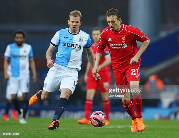 Lucas Leiva of Liverpool evades Jordan Rhodes of Blackburn Rovers during the FA Cup Quarter Final Replay match between Blackburn Rovers and Liverpool...