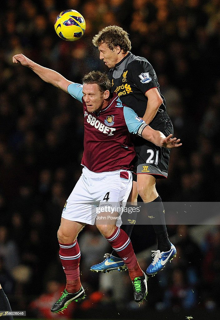 Lucas Leiva of Liverpool goes up with Kevin Nolan of West Ham United during the Barclays Premier League match between West Ham United and Liverpool at Boleyn Ground on December 9, 2012 in London, England.