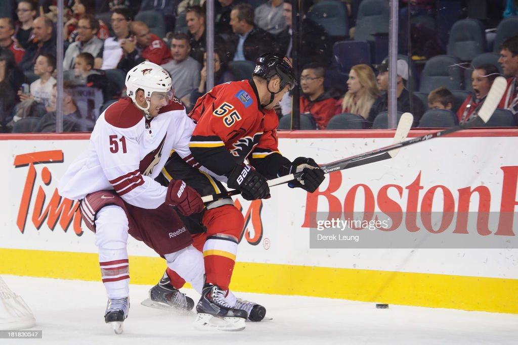 Lucas Lessio #51 of the Phoenix Coyotes ties up <a gi-track='captionPersonalityLinkClicked' href=/galleries/search?phrase=Shane+O%27Brien&family=editorial&specificpeople=2190942 ng-click='$event.stopPropagation()'>Shane O'Brien</a> #55 of the Calgary Flames to stop him from getting the puck during a preseason NHL game at Scotiabank Saddledome on September 25, 2013 in Calgary, Alberta, Canada.
