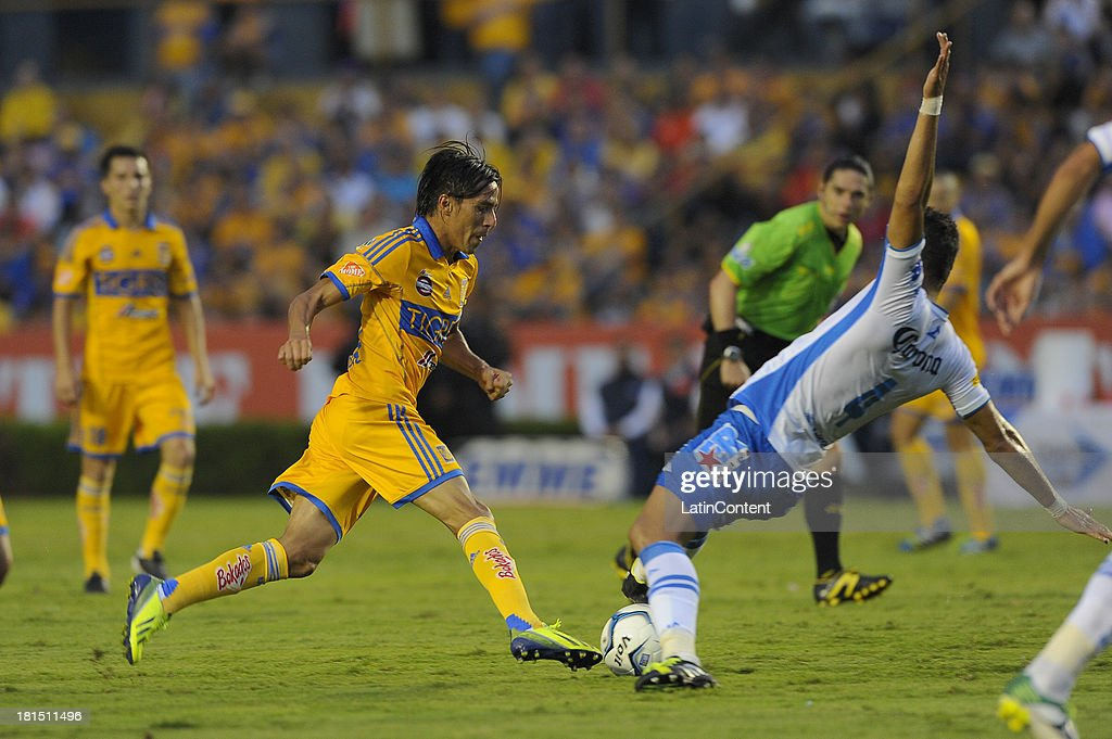 Lucas Lobos of Tigres fights for the ball with Jesús Chávez of Puebla during a match between Tigres UANL and Puebla FC as part of the Liga MX at Universitario stadium on September 21, 2013 in Monterrey, Mexico.