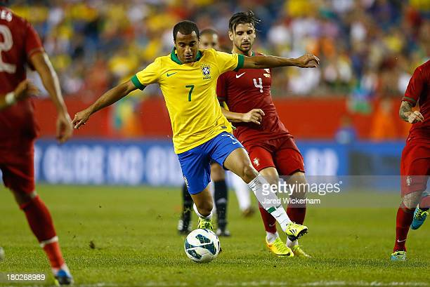 Lucas Moura of Brazil carries the ball past Miguel Veloso of Portugal in the second half during the international friendly match at Gillette Stadium...