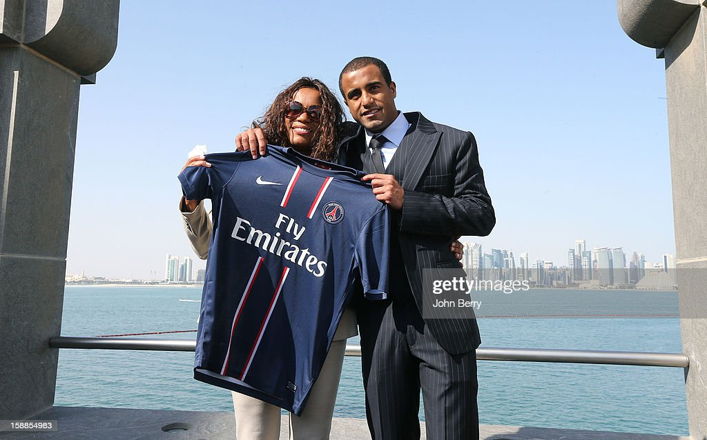 Lucas Moura of PSG holds a shirt as he poses with his mother Maria de Fatima during his official unveiling as a player of Paris Saint-Germain at a press conference and a jersey presentation at the Museum of Islamic Art on January 1, 2013 in Doha, Qatar.