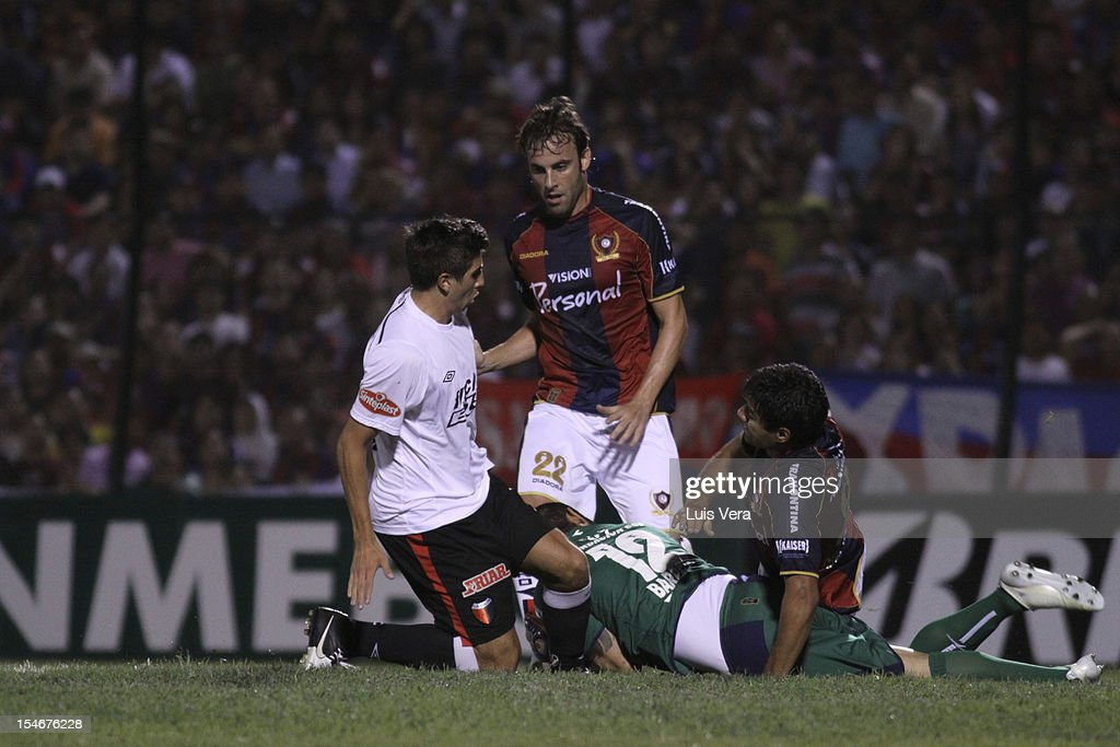 Lucas Mugni (L) of Colon fights for the ball with Santiago Uglessich (C) and <a gi-track='captionPersonalityLinkClicked' href=/galleries/search?phrase=Diego+Barreto&family=editorial&specificpeople=2939685 ng-click='$event.stopPropagation()'>Diego Barreto</a> (C) of Cerro during the Bridgestone Sudamericana 2012 Cup at Gral Pablo Rojas Stadium on October 23, 2012 in Asuncion, Paraguay.