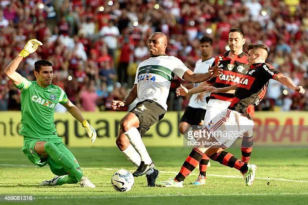 Lucas Mugni of Flamengo battles for the ball with Luccas Claro and goalkeeper Vanderlei of Coritiba during a match between Flamengo and Coritiba as...
