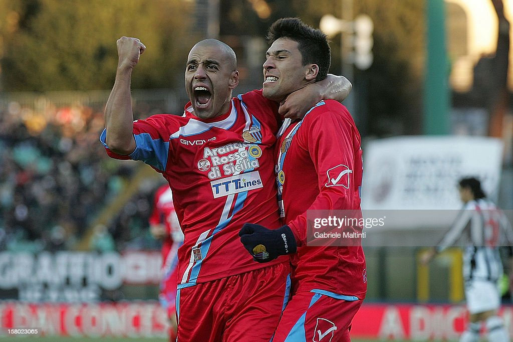 Lucas Nahuel Castro of Calcio Catania celebrates with teammate Sergio Beernardo Almiron after scoring their first goal during the Serie A match...