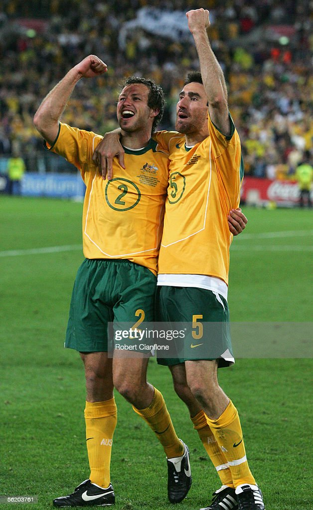 Lucas Neill #2 and Tony Vidmar #5 for the Socceroos celebrates after winning the second leg of the 2006 FIFA World Cup qualifying match between Australia and Uruguay at Telstra Stadium November 16, 2005 in Sydney, Australia.