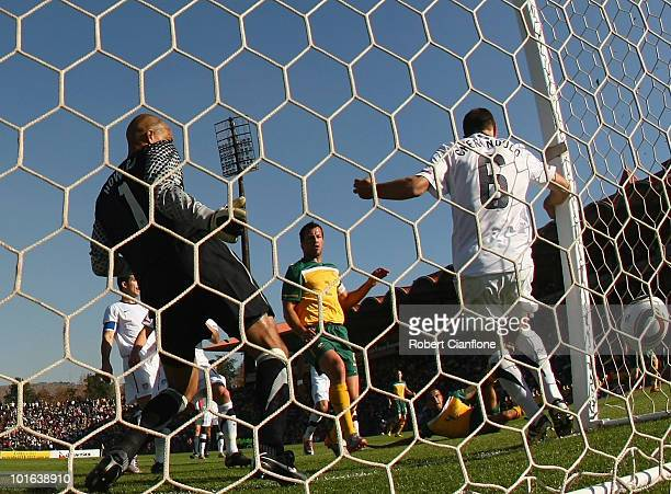 Lucas Neill of Australia celebrates as Tim Cahill of Australia scores past USA goalkeeper Timothy Howard and player Steven Cherundolo during the...
