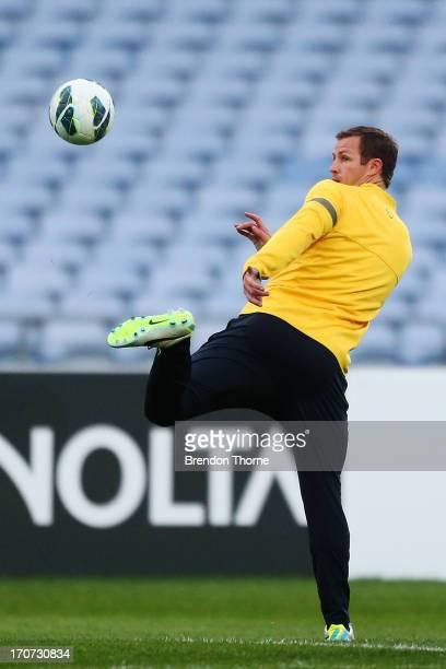 Lucas Neill of Australia kicks a ball during an Australian Socceroos training session at ANZ Stadium on June 17 2013 in Sydney Australia