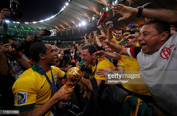 Lucas of Brazil celebrates with the trophy at the end of the FIFA Confederations Cup Brazil 2013 Final match between Brazil and Spain at Maracana on...