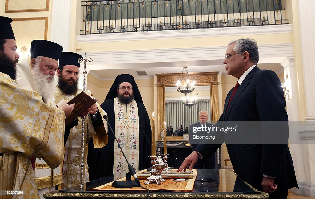 Lucas Papademos, former vice president of the European Central Bank (ECB), right, is sworn in as Greece's prime minister by Orthodox priests while Karolos Papoulias, Greece's president, second right, looks on in Athens, Greece, on Friday, Nov. 11, 2011. Papademos said a sense of unity will assist him and his new interim government to achieve its goals. Photographer: Kostas Tsironis/Bloomberg via Getty Images