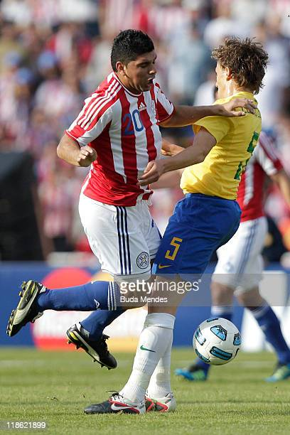 Lucas Pezzini of Brazil struggles for the ball with Nestor Ortigoza of Paraguay during a match as part of Group B of Copa America 2011 at the Mario...