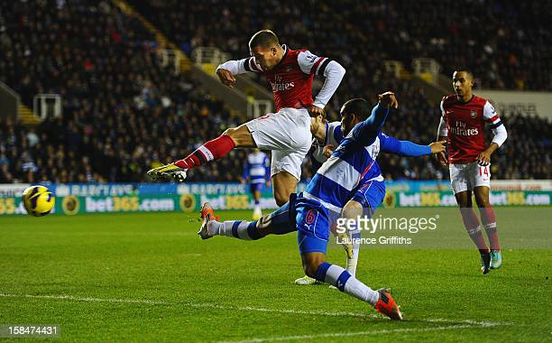 Lucas Podolski of Arsenal fires the ball home to score the opening goal during the Barclays Premier League match between Reading and Arsenal at...