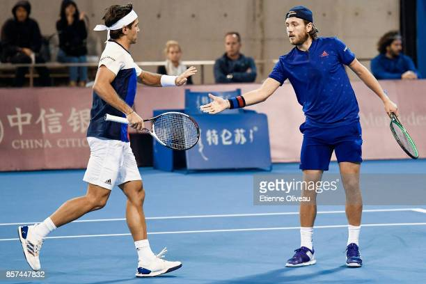 Lucas Pouille of France and Fernando Verdasco of Spain check hands during their Men's double first round match against Jack Sock and John Isner of...