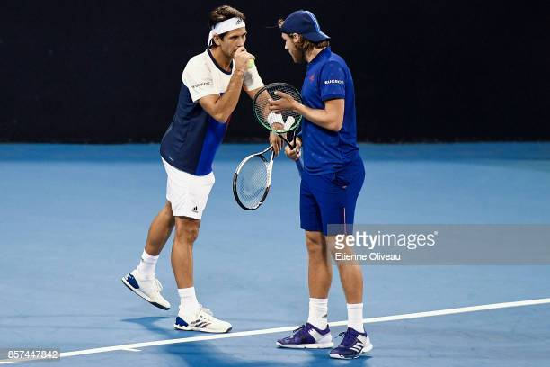 Lucas Pouille of France and Fernando Verdasco of Spain talk tacticts during their Men's double first round match against Jack Sock and John Isner of...