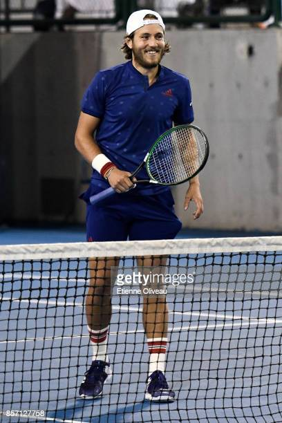 Lucas Pouille of France partner of Fernando Verdasco of Spain smiles after scoring a point against Roberto Bautista Agut of Spain and Aljaz Bedene of...