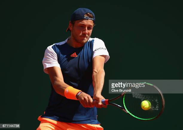 Lucas Pouille of France plays a backhand against Pablo Cuevas of Uruguay in their quarter final round match on day six of the Monte Carlo Rolex...