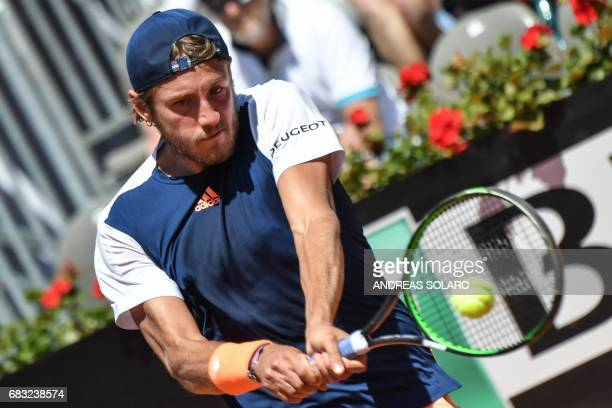 Lucas Pouille of France returns the ball to Sam Querrey of US during their ATP Tennis Open tournament match at the Foro Italico in Rome on May 15...