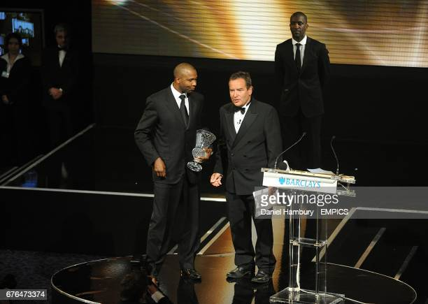 Lucas Radebe collects his Special Merit Award award on stage with Jeff Stelling at the PFA Player of the Year Awards 2010 at the Grosvenor House...