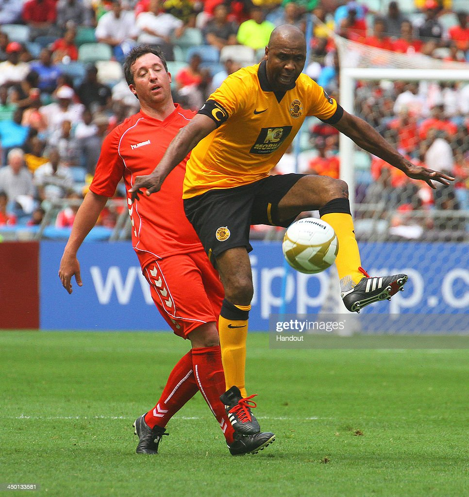 Lucas Radebe holds off Robbie Fowler during the Legends match between Liverpool FC Legends and Kaizer Chiefs Legends at Moses Mabhida Stadium on November 16, 2013 in Durban, South Africa.