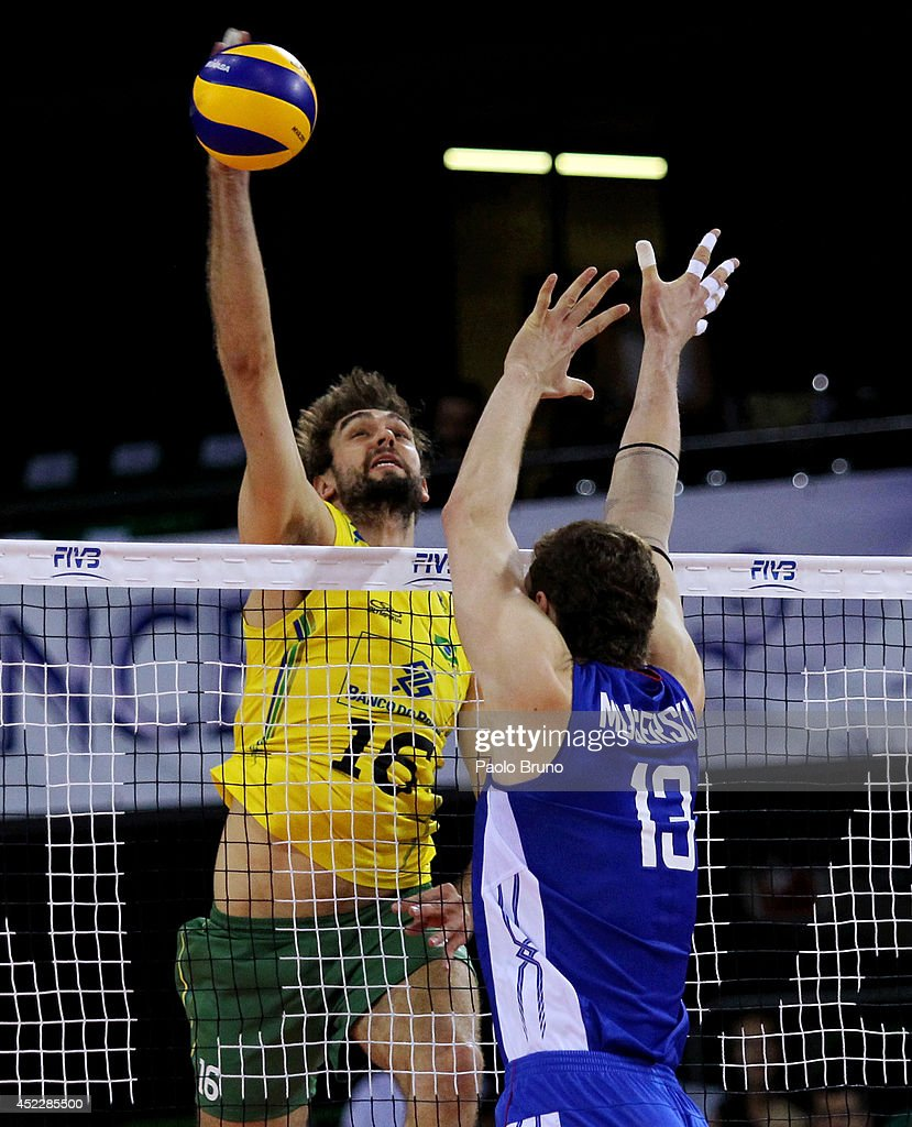 Lucas Saatkamp of Brazil spikes the ball as <a gi-track='captionPersonalityLinkClicked' href=/galleries/search?phrase=Dmitriy+Muserskiy&family=editorial&specificpeople=7112660 ng-click='$event.stopPropagation()'>Dmitriy Muserskiy</a> of Russia blocks during the FIVB World League Final Six match between Russia and Brazil at Mandela Forum on July 17, 2014 in Florence, Italy.