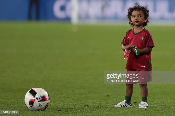 Lucas son of Portugal's forward Nani stands on the pitch after the round of sixteen football match Croatia against Portugal of the Euro 2016 football...