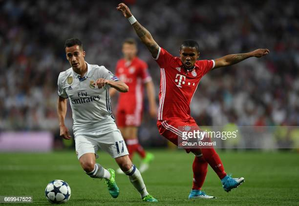 Lucas Vazquez of Real Madrid attempts to get past Douglas Costa of Bayern Muenchen during the UEFA Champions League Quarter Final second leg match...