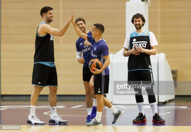 Lucas Vazquez of Real Madrid shakes hands with basketball player Felipe Reyes during a training session at Ciudad Real Madrid basketball court on...