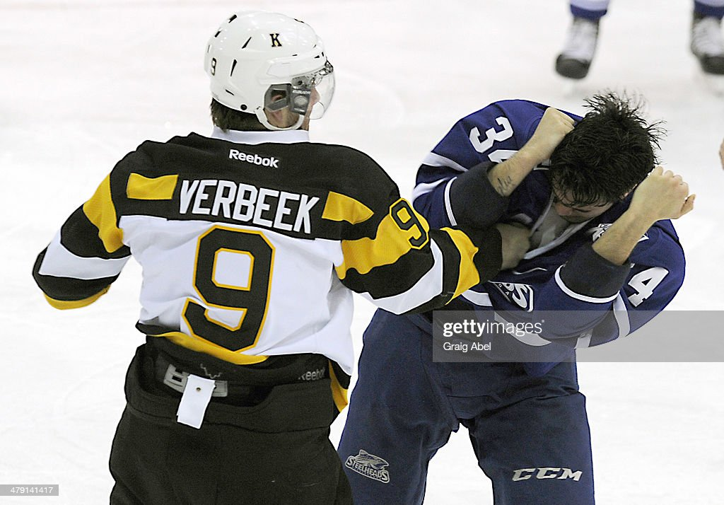 Lucas Venuto #34 of the Mississauga Steelheads covers up during a fight with Ryan Verbeek #9 of the Kingston Frontenacs during game action on March 16, 2014 at the Hershey Centre in Mississauga, Ontario, Canada.