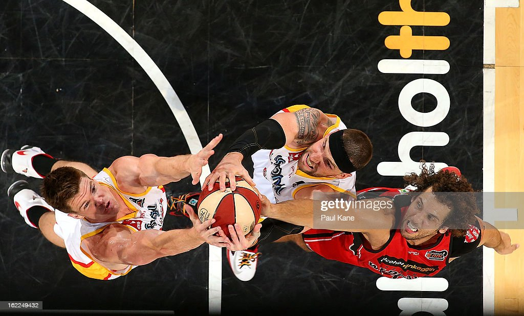 Lucas Walker and Seth Scott of the Tigers contest a rebound against Matthew Knight of the Wildcats during the round 20 NBL match between the Perth Wildcats and the Melbourne Tigers at Perth Arena on February 21, 2013 in Perth, Australia.