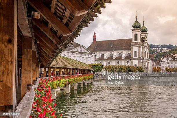 Lucerne medieval wood bridge with flowers and city
