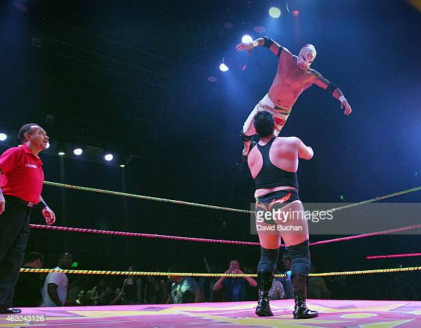 Luchadores Rey Horus jumps onto Bobby Zavala as they perform at Luca VaVOOM Valentine's Show 'Dangerous/Beautiful' at The Mayan on February 11 2015...