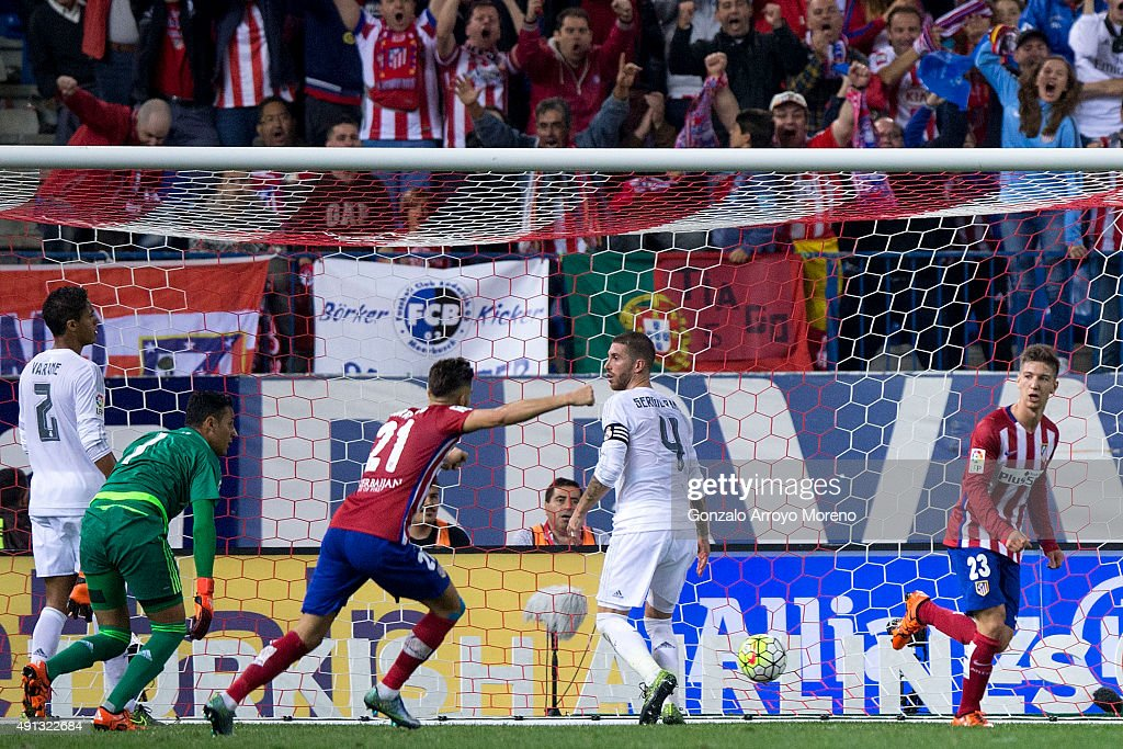 Luciano Dario Vietto (R) of Atletico de Madrid celebrates scoring their opening goal with teammate Yannick Carrasco (3dL) as Sergio Ramos (2ndR) of Real Madrid CF reacts with teammates goalkeeper <a gi-track='captionPersonalityLinkClicked' href=/galleries/search?phrase=Keylor+Navas&family=editorial&specificpeople=2097517 ng-click='$event.stopPropagation()'>Keylor Navas</a> (2ndL) and <a gi-track='captionPersonalityLinkClicked' href=/galleries/search?phrase=Raphael+Varane&family=editorial&specificpeople=7365948 ng-click='$event.stopPropagation()'>Raphael Varane</a> during the La Liga match between Club Atletico de Madrid and Real Madrid CF at Vicente Calderon Stadium on October 4, 2015 in Madrid, Spain.