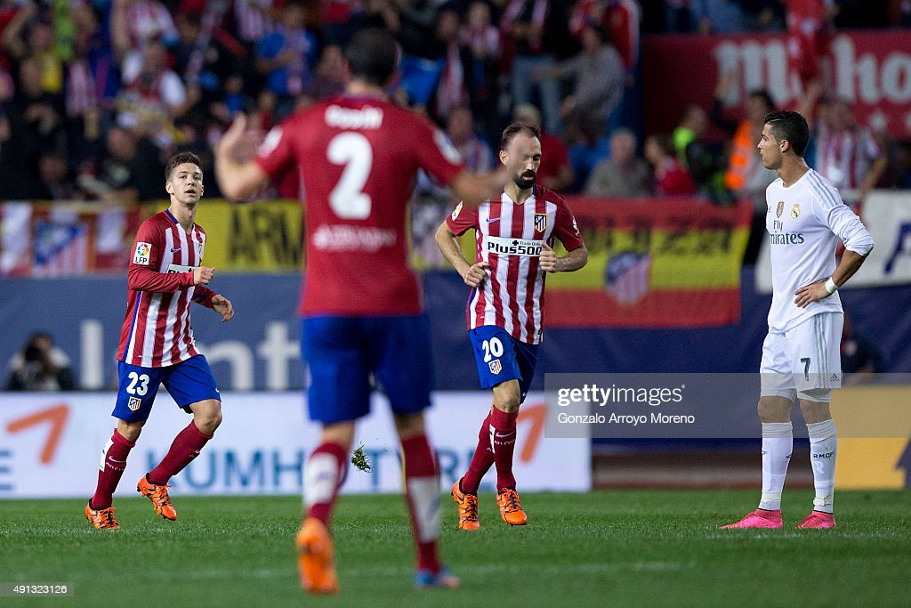 Luciano Dario Vietto (L) of Atletico de Madrid celebrates scoring their opening goal with teammates Juan Francisco Torres alias <a gi-track='captionPersonalityLinkClicked' href=/galleries/search?phrase=Juanfran+-+Soccer+Right+Back+born+1985&family=editorial&specificpeople=2634439 ng-click='$event.stopPropagation()'>Juanfran</a> (3dL) and <a gi-track='captionPersonalityLinkClicked' href=/galleries/search?phrase=Diego+Godin&family=editorial&specificpeople=608999 ng-click='$event.stopPropagation()'>Diego Godin</a> (2ndL) as <a gi-track='captionPersonalityLinkClicked' href=/galleries/search?phrase=Cristiano+Ronaldo+-+Soccer+Player&family=editorial&specificpeople=162689 ng-click='$event.stopPropagation()'>Cristiano Ronaldo</a> (R) of Real Madrid CF reacts during the La Liga match between Club Atletico de Madrid and Real Madrid CF at Vicente Calderon Stadium on October 4, 2015 in Madrid, Spain.