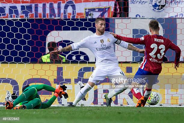 Luciano Dario Vietto of Atletico de Madrid scores their opening goal against Sergio Ramos of Real Madrid CF and his teammate goalkeeper Keylor Navas...