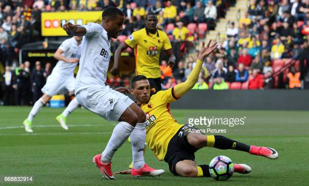 Luciano Narsingh of Swansea City is challenged by Jose Holebas of Watford during the Premier League match between Watford and Swansea City at...