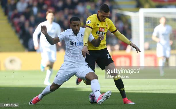 Luciano Narsingh of Swansea City is closely marked by Jose Holebas of Watford during the Premier League match between Watford and Swansea City at...