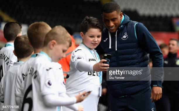 Luciano Narsingh of Swansea City takes a selfie photograph with a fan as he arrvies at the stadium prior to the Premier League match between Swansea...