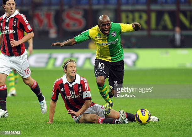 Luciano of AC Chievo Verona is tackled to Massimo Ambrosini of of AC Milan during the Serie A match between AC Milan and AC Chievo Verona at San Siro...