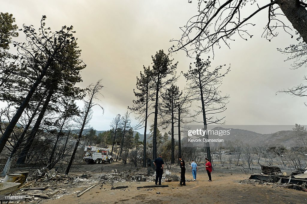 Lucille Prevosto and her husband Joe Prevosto and a couple of firefighters survey the damage in the charred remains of their son's Marty Prevosto's property, which was destroyed by the Mountian Fire July 18, 2013 near Idyllwild, California. The massive wildfire in Riverside county has grown to 23,000 acres and is advancing towards the mountain town of Idyllwild on one front and city of Palm Springs on the other front destroying several homs and forcing the evacuation of 6,000 people.